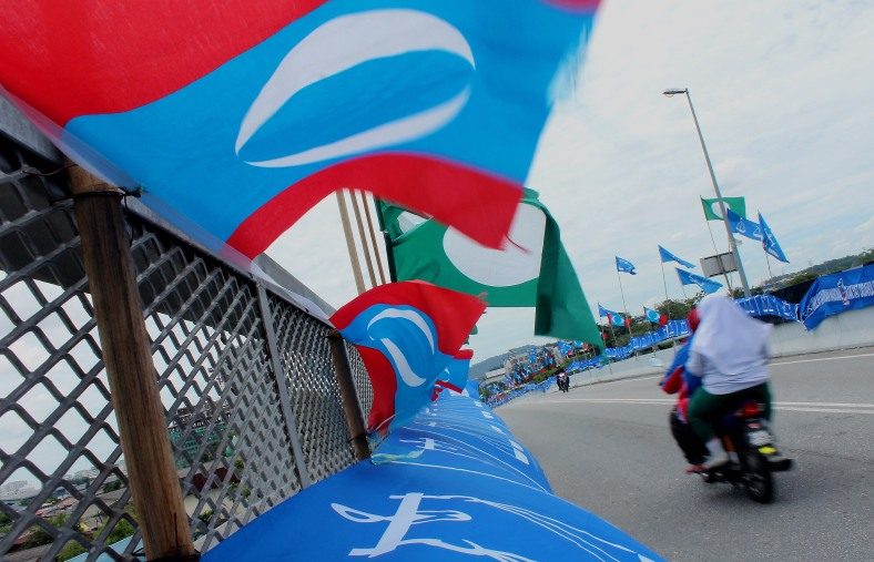 SHAH ALAM 1 May 2013. A motorcyclist rides past a row of party flags at Padang Jawa ahead of the 13th General Election (GE-13). The general election has been set on May 5 in Malaysia. Photo Adib Rawi Yahya