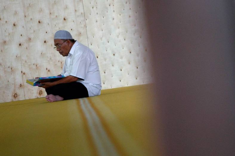 KUALA LUMPUR 10 July 2013. A Muslim men reading quran while waiting for breaking fast on the first day of holy month of Ramadan at Jamek mosque, Kampung Baru. Ramadan is the ninth month of the Islamic calendar, Islam's holy month of Ramadan is celebrated by Muslims worldwide marked by fasting, abstaining from foods, sex and smoking from dawn to dusk for soul cleansing and strengthening the spiritual bond between them and the Almighty. Photo Adib Rawi Yahya