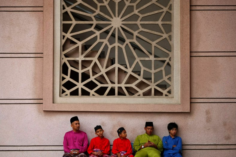 A group of muslim men sitting outside the mosque while waiting to perform prayers during the Eid al-Adha festival at Putrajaya outside Kuala Lumpur on October 15, 2013. Eid al-Adha is an important religious holiday celebrated by Muslims worldwide to honour the willingness of the prophet Abraham to sacrifice his young first-born son Ismail a as an act of submission to Allah's command and his son's acceptance to being sacrificed, before Allah intervened to provide Abraham with a lamb to sacrifice instead. Photo Adib Rawi Yahya