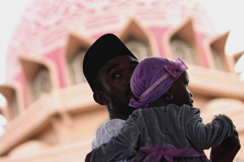 A man carries his daughter when attended the mosque for prayers during the Eid al-Adha festival at Putrajaya outside Kuala Lumpur on October 15, 2013. Eid al-Adha is an important religious holiday celebrated by Muslims worldwide to honour the willingness of the prophet Abraham to sacrifice his young first-born son Ismail a as an act of submission to Allah's command and his son's acceptance to being sacrificed, before Allah intervened to provide Abraham with a lamb to sacrifice instead. Photo Adib Rawi Yahya
