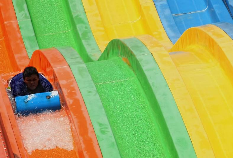 Visitors play waterslide to cool off due to rising temperatures outside Kuala Lumpur October 16, 2013. Global temperature change caused by global warming continues, the earth's temperature has increased by two degrees and the rates vary by continent and region specific. Photo Adib Rawi Yahya