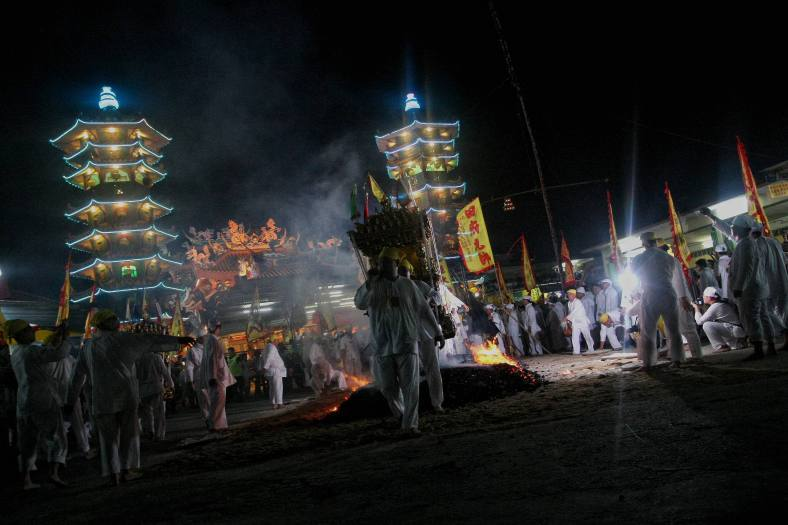 "Malaysian Chinese devotees carrying an ""Emperor God"" while walking barefoot over burning coals during Chinese Nine Emperor Gods Festival at Nine Emperor Gods temple outside Kuala Lumpur on October 13, 2013. The nine-day Taoist festival, believers welcome the ""emperor gods"" who they believe live amongst the stars, in order to bring good fortune, longevity and good health. Some devotees stay at a temple during the festival, which begins on the eve of the ninth lunar month of the Chinese calendar, where they consume vegetarian meals and recite continuous prayers. Photo Adib Rawi Yahya"
