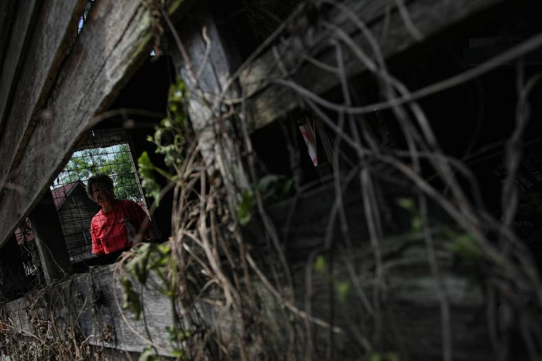 A residents look dilapidated sundry shop omitted her grandfather at Kampung Hakka on November 8, 2013. Kampung Hakka has a trace of history as long as the 1860. There are more than 50 low income group families who reside in the village, its surrounding area used to be tin mines where the British brought in labourers from China who reigned from Hui Zhou, China, they used to live in a nearby area called Kampung Attap that has taken the name Kampung Hakka today. Photo Adib Rawi Yahya