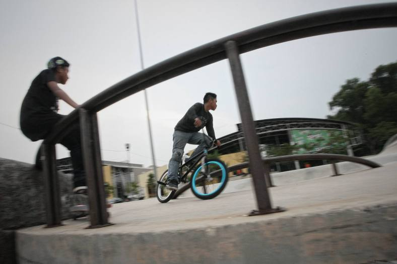 A boy doing stunt jumps with a bike during school holiday outside Kuala Lumpur on November 25, 2013. Malaysian public schools are closed for the year-end holidays. photo Adib Rawi Yahya