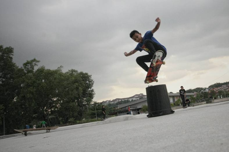 A boy doing stunt with his skateboard during school holiday outside Kuala Lumpur on November 25, 2013. Malaysian public schools are closed for the year-end holidays. photo Adib Rawi Yahya