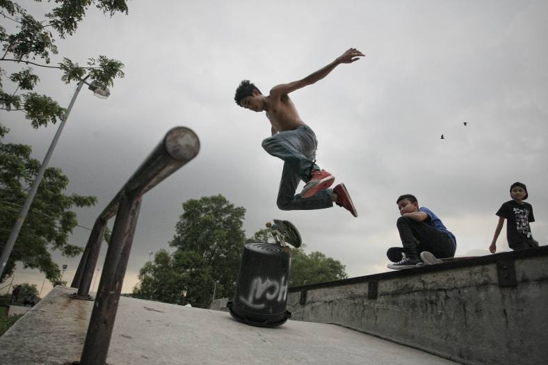 A boy doing stunt jumps with his skateboard during school holiday outside Kuala Lumpur on November 25, 2013. Malaysian public schools are closed for the year-end holidays. photo Adib Rawi Yahya