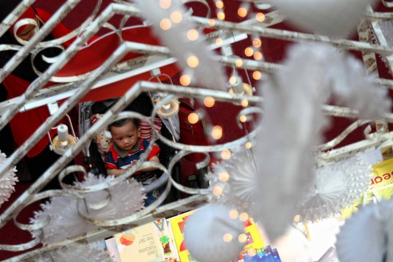 A kid seeing the Christmas decorations at a shopping mall inside Kuala Lumpur on 18 December, 2013. Christmas is the biggest festival of Christians, is celebrated every year on December 25 to commemorate the birth (in which the facts, the date is not the date of his birth) Jesus Christ, also known as Jesus of Nazareth, the founder of the Christian message. According to the Bible, New Testament, Jesus was born to Mary (Virgin Mary) in Jerusalem. Christians believe that Jesus' birth was within Judaism predictions about the coming of a savior (Messiah) from a chronology of King David, whose coming was to redeem mankind from Adam's sin (original sin). Photo Adib Rawi Yahya