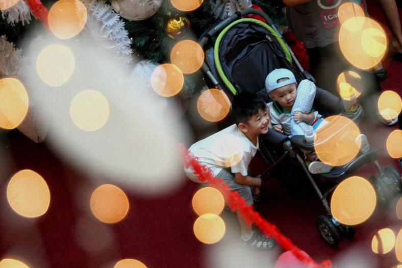 A kid taking pictures with Christmas decorations at a shopping mall inside Kuala Lumpur on 18 December, 2013. Christmas is the biggest festival of Christians, is celebrated every year on December 25 to commemorate the birth (in which the facts, the date is not the date of his birth) Jesus Christ, also known as Jesus of Nazareth, the founder of the Christian message. According to the Bible, New Testament, Jesus was born to Mary (Virgin Mary) in Jerusalem. Christians believe that Jesus' birth was within Judaism predictions about the coming of a savior (Messiah) from a chronology of King David, whose coming was to redeem mankind from Adam's sin (original sin). Photo Adib Rawi Yahya