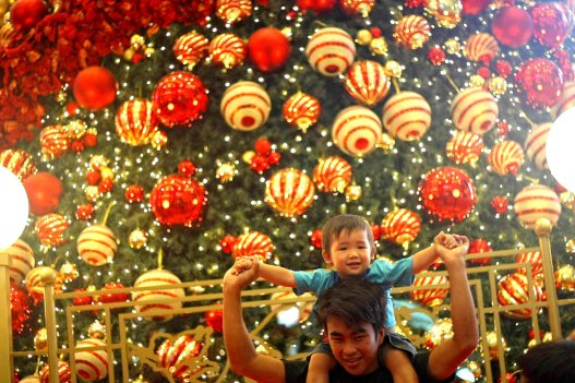 People playing near the Christmas tree decorations at a shopping mall inside Kuala Lumpur on 18 December, 2013. Christmas is the biggest festival of Christians, is celebrated every year on December 25 to commemorate the birth (in which the facts, the date is not the date of his birth) Jesus Christ, also known as Jesus of Nazareth, the founder of the Christian message. According to the Bible, New Testament, Jesus was born to Mary (Virgin Mary) in Jerusalem. Christians believe that Jesus' birth was within Judaism predictions about the coming of a savior (Messiah) from a chronology of King David, whose coming was to redeem mankind from Adam's sin (original sin). Photo Adib Rawi Yahya