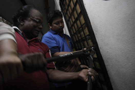 Enforcement officers cut through locks after the tenants failed to answer the door during a crackdown against illegal immigrants at City Hall flats near Kuala Lumpur on December 18, 2013. Five tenants of City Hall flats at Sentul have been blacklisted by the City Hall for sub-letting their units to illegal foreign immigrants. 11 foreigners comprising five Indian nationals, five Bangladeshis and one Indonesian were nabbed by the authorities in this operation. Photo Adib Rawi Yahya