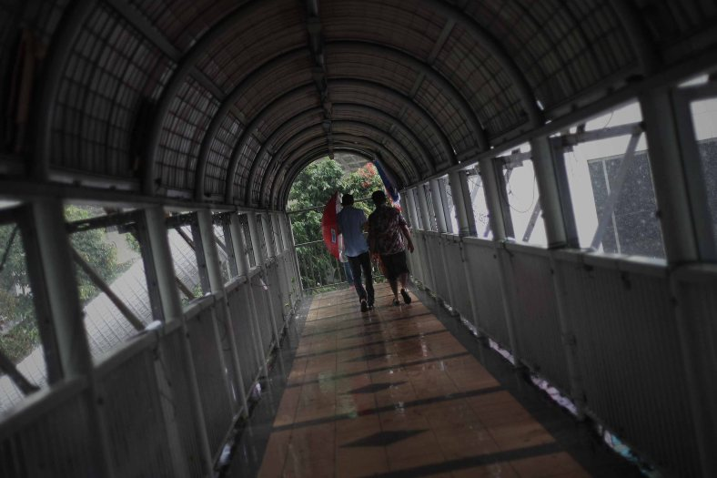Pedestrians cross overhead bridge when downpour at Kuala Lumpur on December 20, 2013. Rain can fall at almost any time of the year, Kuala Lumpur receives rain on about 200 days of the year. Temperatures in Kuala Lumpur are fairly steady throughout the year, averaging between 22°C and 32°C. Photo Adib Rawi Yahya