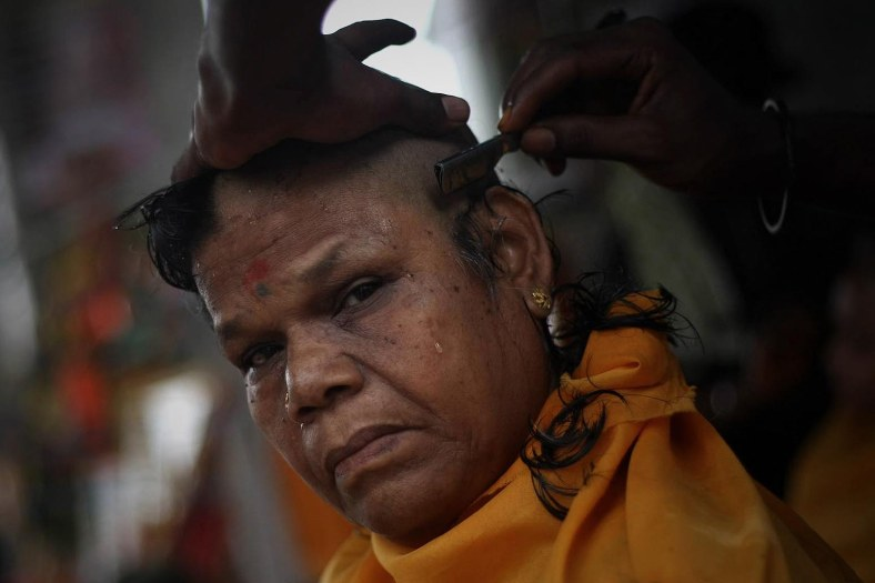 A Hindu devotee get their head shave to perform their religious rites during the Thaipusam festival at the Batu Caves on the outskirts of Kuala Lumpur on January 17, 2014. The Hindu festival of Thaipusam, which commemorates the day when Goddess Pavarthi gave her son Lord Muruga an invincible lance with which he destroyed evil demons, is celebrated by some two million ethnic Indians in Malaysia and Singapore. Photo Adib Rawi Yahya