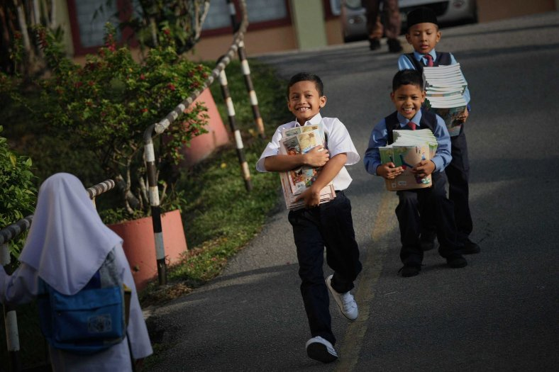 Behavior some pupils help the teacher brings textbooks during on the first day of school session outside Kuala Lumpur on January 01, 2014. Selangor received nearly half a million primary school pupils enrolled in the school session 2014. Photo Adib Rawi Yahya