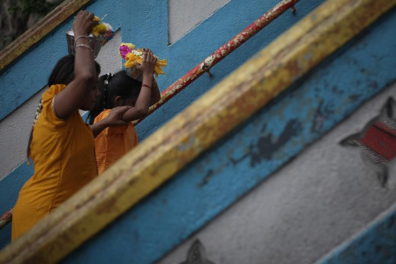 Hindu devotees carries a milk pot on her head to perform their religious rites during the Thaipusam festival at the Batu Caves on the outskirts of Kuala Lumpur on January 17, 2014. The Hindu festival of Thaipusam, which commemorates the day when Goddess Pavarthi gave her son Lord Muruga an invincible lance with which he destroyed evil demons, is celebrated by some two million ethnic Indians in Malaysia and Singapore. Photo Adib Rawi Yahya