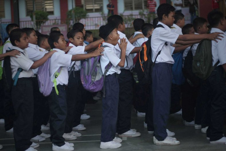 Behavior primary school pupils while attend an early morning gathering during on the first day of school session outside Kuala Lumpur on January 01, 2014. Selangor received nearly half a million primary school pupils enrolled in the school session 2014. Photo Adib Rawi Yahya