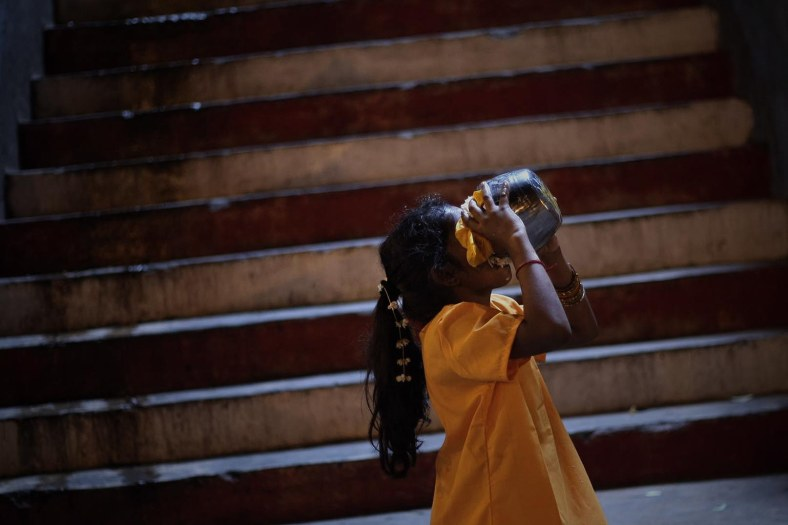 A young devotee drank the milk after perform their religious rites during the Thaipusam festival at the Batu Caves on the outskirts of Kuala Lumpur on January 17, 2014. The Hindu festival of Thaipusam, which commemorates the day when Goddess Pavarthi gave her son Lord Muruga an invincible lance with which he destroyed evil demons, is celebrated by some two million ethnic Indians in Malaysia and Singapore. Photo Adib Rawi Yahya