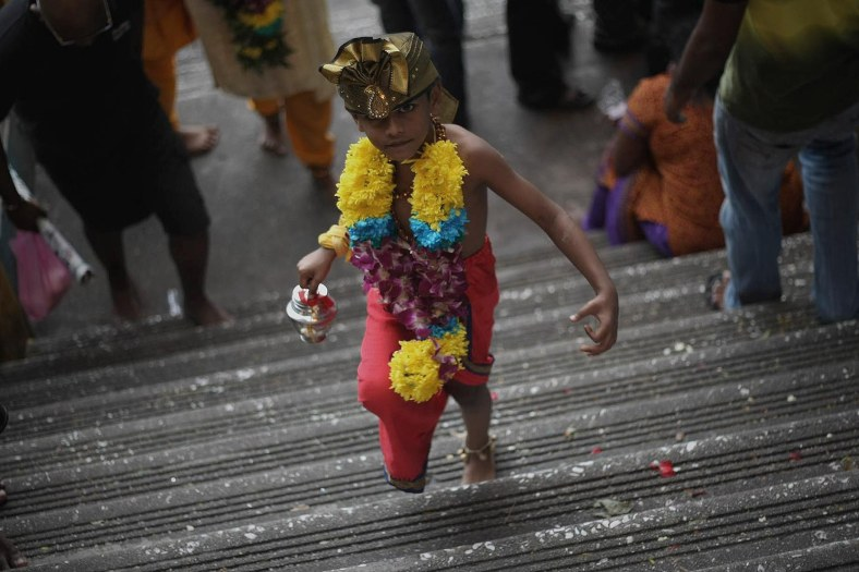 A young devotee walking up the stairs to perform their religious rites during the Thaipusam festival at the Batu Caves on the outskirts of Kuala Lumpur on January 17, 2014. The Hindu festival of Thaipusam, which commemorates the day when Goddess Pavarthi gave her son Lord Muruga an invincible lance with which he destroyed evil demons, is celebrated by some two million ethnic Indians in Malaysia and Singapore. Photo Adib Rawi Yahya