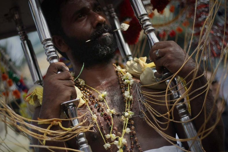 A Hindu devotee restrained with hooks pierced through his body, make their way towards the Batu Caves to perform their religious rites during the Thaipusam festival at the Batu Caves on the outskirts of Kuala Lumpur on January 17, 2014. The Hindu festival of Thaipusam, which commemorates the day when Goddess Pavarthi gave her son Lord Muruga an invincible lance with which he destroyed evil demons, is celebrated by some two million ethnic Indians in Malaysia and Singapore. Photo Adib Rawi Yahya