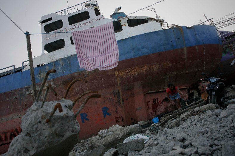 A resident do a daily activities next to cargo ships washed ashore at the height of super Typhoon Haiyan, along the coastal area of Tacloban City, Leyte province, in central Philippines on March 7, 2014. Typhoon Haiyan, one of the most powerful typhoons ever recorded, hit into central Philippine provinces, and left a wide destruction. The United Nations warned on February 15 2014 that millions of survivors of the Philippines deadliest typhoon were still without adequate shelter 100 days after the disaster. Photo Adib Rawi Yahya