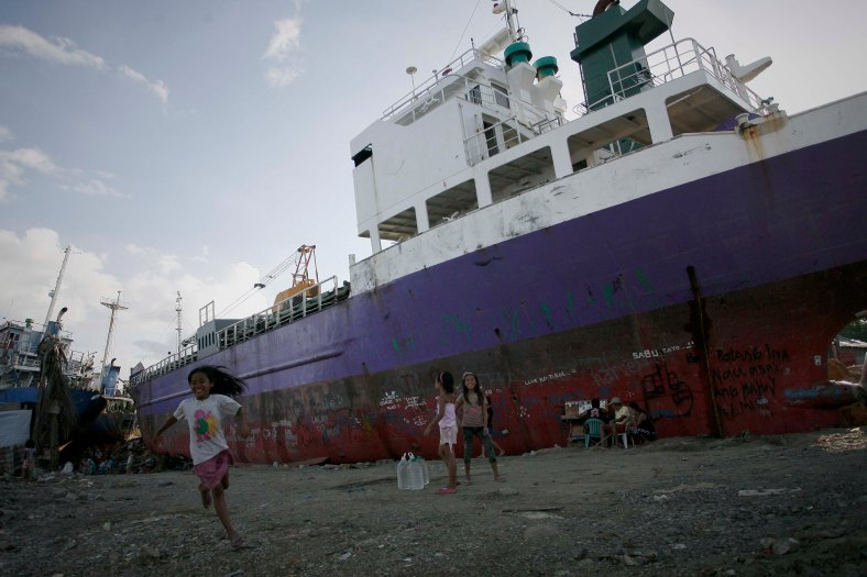 A young-survivor of super Typhoon Haiyan play next to cargo ships washed ashore at the height of super Typhoon Haiyan, along the coastal area of Tacloban City, Leyte province, in central Philippines on March 7, 2014. Typhoon Haiyan, one of the most powerful typhoons ever recorded, hit into central Philippine provinces, and left a wide destruction. The United Nations warned on February 15 2014 that millions of survivors of the Philippines deadliest typhoon were still without adequate shelter 100 days after the disaster. Photo Adib Rawi Yahya