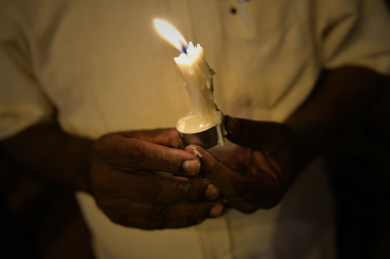 A man prays during a candlelight vigil session for the missing Malaysia Airlines Flight 370 in Kuala Lumpur on April 7, 2014. According to the head of multinational search team, ships and planes have been sent to investigate the electronic pulse signal, which was detected by a Chinese ship for the missing Flight370 aircraft. The MH370 flight with 239 passengers and crew on board went missing since March 8 after taking off from the Kuala Lumpur International Airport. Photo Adib Rawi Yahya