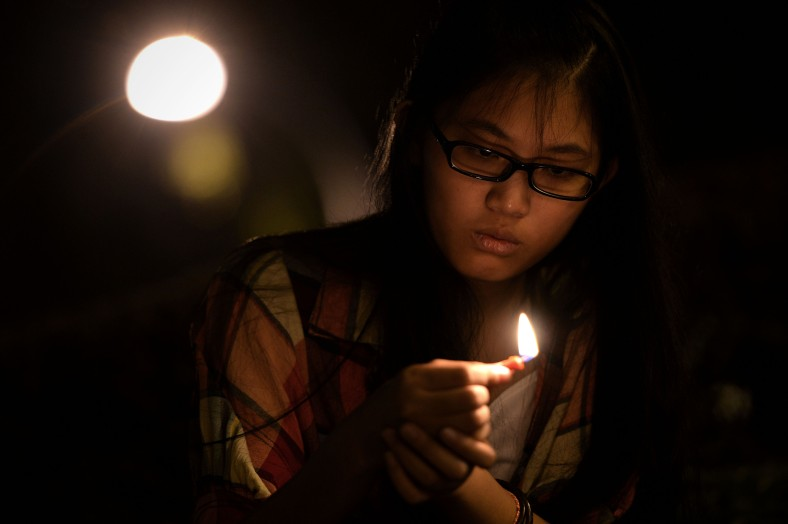 A woman prays during a candlelight vigil session for the missing Malaysia Airlines Flight 370 in Kuala Lumpur on April 7, 2014. According to the head of multinational search team, ships and planes have been sent to investigate the electronic pulse signal, which was detected by a Chinese ship for the missing Flight370 aircraft. The MH370 flight with 239 passengers and crew on board went missing since March 8 after taking off from the Kuala Lumpur International Airport. Photo Adib Rawi Yahya