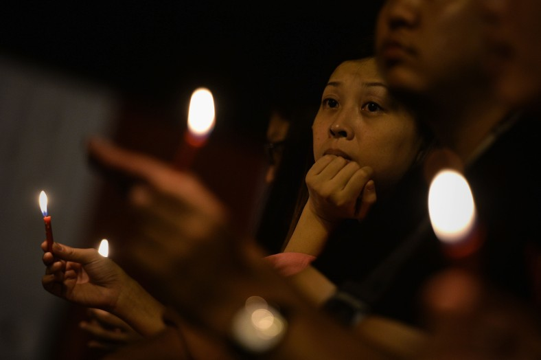 A woman take part during a candlelight vigil session for the missing Malaysia Airlines Flight 370 in Kuala Lumpur on April 7, 2014. According to the head of multinational search team, ships and planes have been sent to investigate the electronic pulse signal, which was detected by a Chinese ship for the missing Flight370 aircraft. The MH370 flight with 239 passengers and crew on board went missing since March 8 after taking off from the Kuala Lumpur International Airport. Photo Adib Rawi Yahya