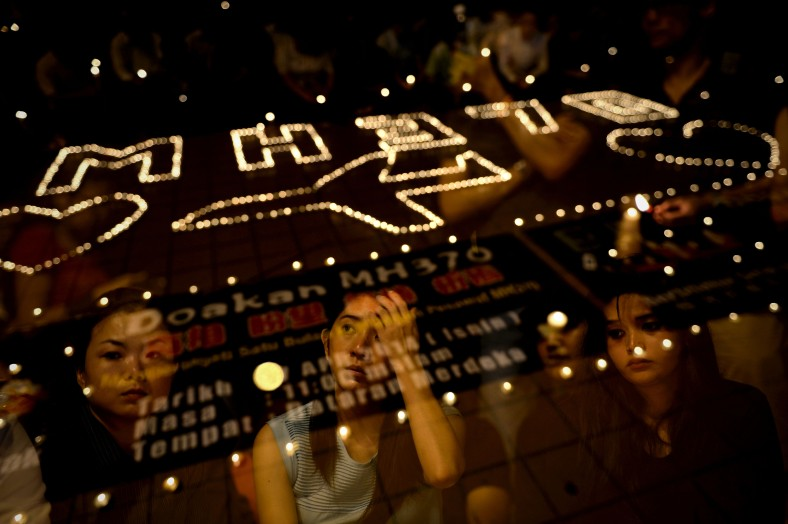 A picture taken with the multiple exposure function of the camera shows participants take part during a candlelight vigil session for the missing Malaysia Airlines Flight 370 in Kuala Lumpur on April 7, 2014. According to the head of multinational search team, ships and planes have been sent to investigate the electronic pulse signal, which was detected by a Chinese ship for the missing Flight370 aircraft. The MH370 flight with 239 passengers and crew on board went missing since March 8 after taking off from the Kuala Lumpur International Airport. Photo Adib Rawi Yahya