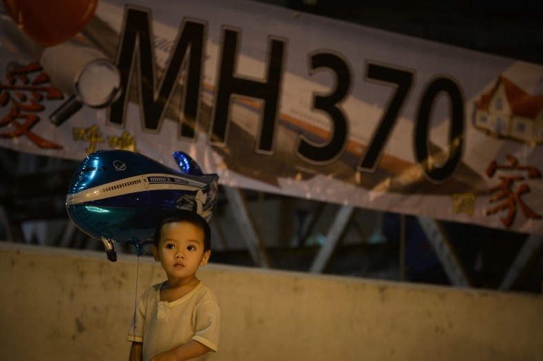 A kid holding a baloon during a candlelight vigil session for the missing Malaysia Airlines Flight 370 in Kuala Lumpur on April 7, 2014. According to the head of multinational search team, ships and planes have been sent to investigate the electronic pulse signal, which was detected by a Chinese ship for the missing Flight370 aircraft. The MH370 flight with 239 passengers and crew on board went missing since March 8 after taking off from the Kuala Lumpur International Airport. Photo Adib Rawi Yahya