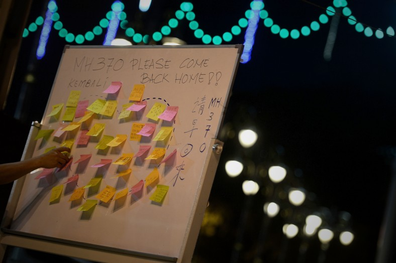 A man leave their quotes on the well-wishes board for the missing passengers during a candlelight vigil session for the missing Malaysia Airlines Flight 370 in Kuala Lumpur on April 7, 2014. According to the head of multinational search team, ships and planes have been sent to investigate the electronic pulse signal, which was detected by a Chinese ship for the missing Flight370 aircraft. The MH370 flight with 239 passengers and crew on board went missing since March 8 after taking off from the Kuala Lumpur International Airport. Photo Adib Rawi Yahya