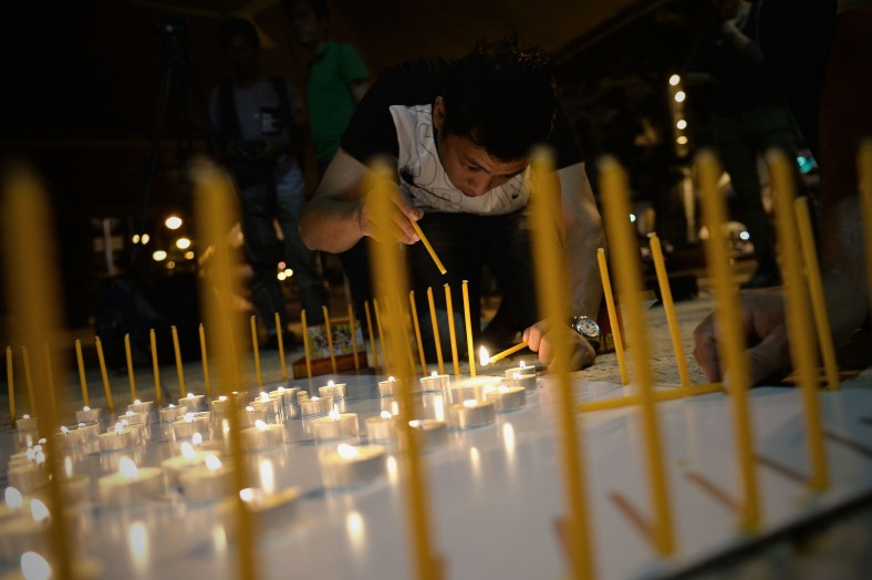 A man take part during a candlelight vigil session for the missing Malaysia Airlines Flight 370 in Kuala Lumpur on April 7, 2014. According to the head of multinational search team, ships and planes have been sent to investigate the electronic pulse signal, which was detected by a Chinese ship for the missing Flight370 aircraft. The MH370 flight with 239 passengers and crew on board went missing since March 8 after taking off from the Kuala Lumpur International Airport. Photo Adib Rawi Yahya