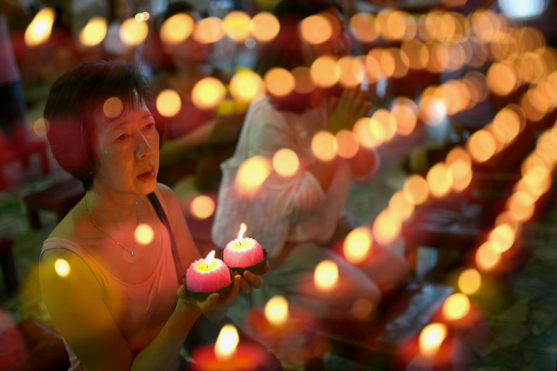 A picture taken with the multiple exposure function of the camera shows a woman offers prays ahead of Wesak Day celebration at Penang on May 13, 2014. Wesak Day which is the most important of the Buddhist festivals and it is a day to pay homage to Lord Buddha on his birthday and to celebrate his attainment of enlightment as well as to commemorate his death. Photo Adib Rawi Yahya