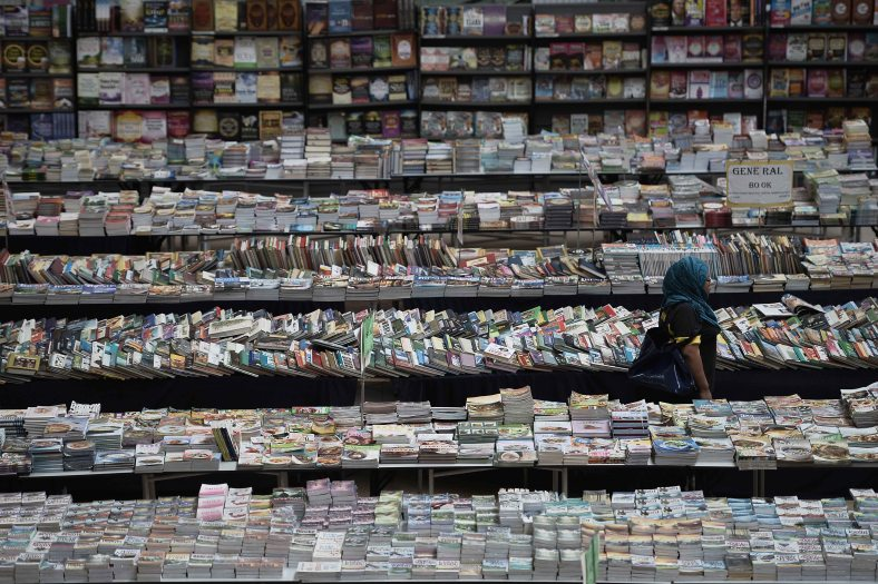 A woman past the sea of books sold at a shopping mall outside Kuala Lumpur on June 17, 2014. Photo Adib Rawi Yahya
