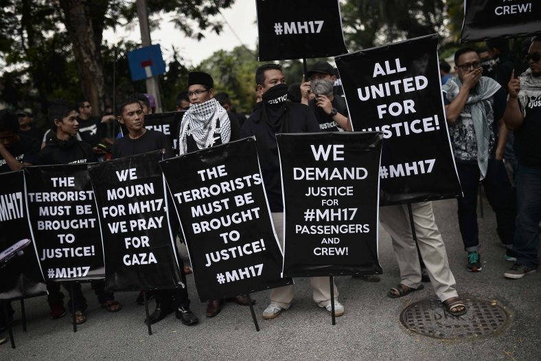 Malaysians protester hold placards during a rally outside the Russian embassy in Kuala Lumpur on July 22, 2014. In frustration over the crash of Malaysia Airlines flight MH17 carrying 298 people from Amsterdam to Kuala Lumpur in an area of eastern Ukraine controlled by Pro-Russian separatists. Rebels controlling the crash site of Malaysian flight MH 17 on July 21 handed over the plane's black boxes, and declared a localised truce to allow international experts full access to the forensic minefield in east Ukraine. Photo Adib Rawi Yahya