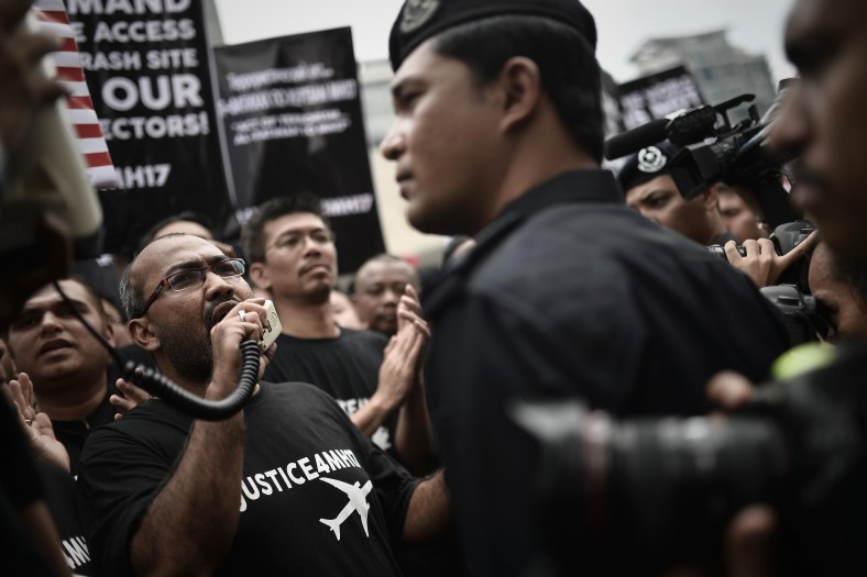 Malaysians protester hold placards during a rally outside the Ukraine embassy in Kuala Lumpur on July 22, 2014. In frustration over the crash of Malaysia Airlines flight MH17 carrying 298 people from Amsterdam to Kuala Lumpur in an area of eastern Ukraine controlled by Pro-Russian separatists. Rebels controlling the crash site of Malaysian flight MH 17 on July 21 handed over the plane's black boxes, and declared a localised truce to allow international experts full access to the forensic minefield in east Ukraine. Photo Adib Rawi Yahya