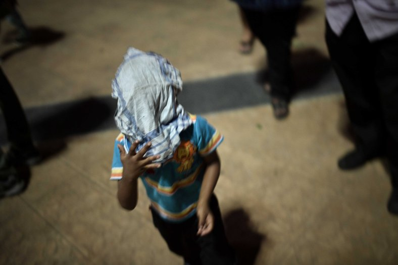 A young kids cover his face with a handkerchief during a special prayer vigil for the ill fated Malaysia Airlines, MH17 in Kuala Lumpur on July 22, 2014. Malaysia Airlines Flight 17 was a scheduled international passenger flight from Amsterdam to Kuala Lumpur that crashed on 17 July 2014. The plane is believed to have been shot down with a Buk surface-to-air missile and killing all 283 passengers and 15 crew on board. The crash occurred in the conflict zone of the ongoing Donbass insurgency, in an area controlled by the Donbass People's Militia. Photo Adib Rawi Yahya