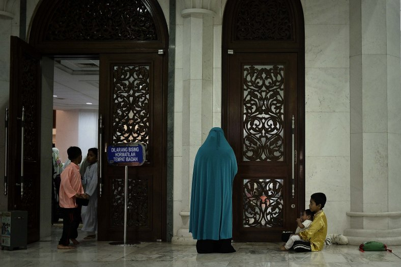 Young Malaysian Muslims children take care of his brother while his mother perform prayers known as Tarawih on the holy Islamic month of Ramadan in Kuala Lumpur on July 02, 2014. Ramadan is the ninth month of the Islamic calendar, Islam's holy month of Ramadan is celebrate by Muslims worldwide mark by fasting, abstain from eating, drinking, having sex and smoking from dawn to dusk to cleanse the soul and strengthen the spiritual bond between them and the almighty. Photo Adib Rawi Yahya