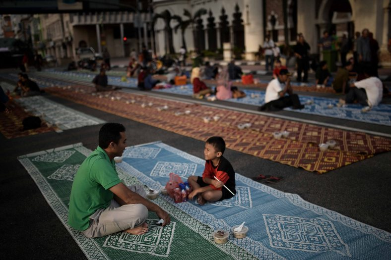 A Malaysian Muslims man talk with his son while wait for the time of breaking fast on the holy Islamic month of Ramadan in Kuala Lumpur on July 05, 2014. Ramadan is the ninth month of the Islamic calendar, Islam's holy month of Ramadan is celebrate by Muslims worldwide mark by fasting, abstain from eating, drinking, having sex and smoking from dawn to dusk to cleanse the soul and strengthen the spiritual bond between them and the almighty. Photo Adib Rawi Yahya