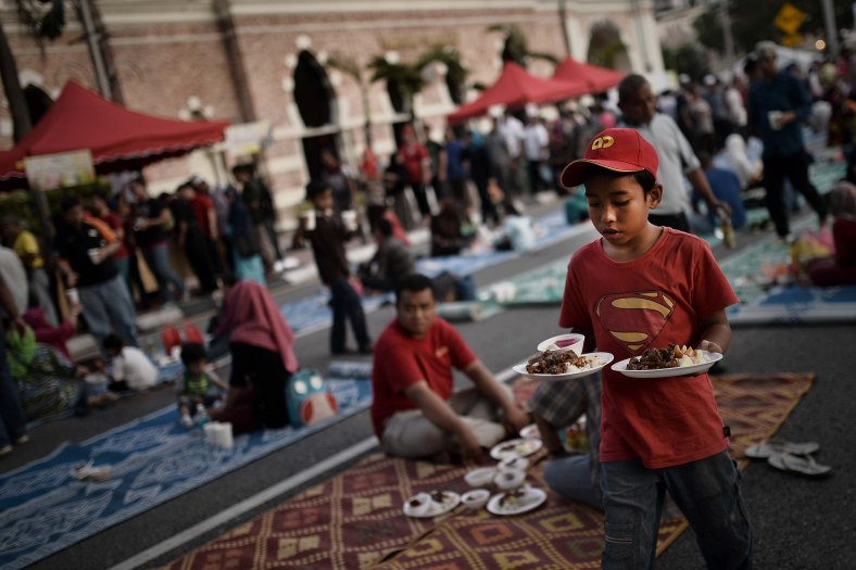 Young Malaysian Muslim children bring food to break fast on the holy Islamic month of Ramadan in Kuala Lumpur on July 05, 2014. Ramadan is the ninth month of the Islamic calendar, Islam's holy month of Ramadan is celebrate by Muslims worldwide mark by fasting, abstain from eating, drinking, having sex and smoking from dawn to dusk to cleanse the soul and strengthen the spiritual bond between them and the almighty. Photo Adib Rawi Yahya