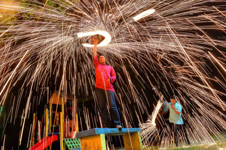 A Muslim man use a soft brush to produce sprinkler firework ahead of Eid al-Fitr celebrations outside Kuala Lumpur on July 26, 2014. Eid al-Fitr is a festival celebrated by Muslims around the world regardless of race, whether Malay, Indian-Muslim and other Muslim nations to mark the end of Ramadan in which Muslims have undergone fasting diligently. It is one of the two biggest festivals for Muslims, as well as Eid al-Adha. Photo Adib Rawi Yahya