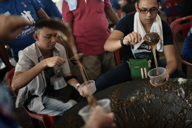Malaysian Muslims cook the famous 'Dodol' dish to be given for breaking fast during the fasting month of ramadan in Kuala Lumpur on July 13, 2014. Dodol is a sweet toffee-like confection, popular in Malaysia that is cooked and distributed during ramadan. Photo Adib Rawi Yahya