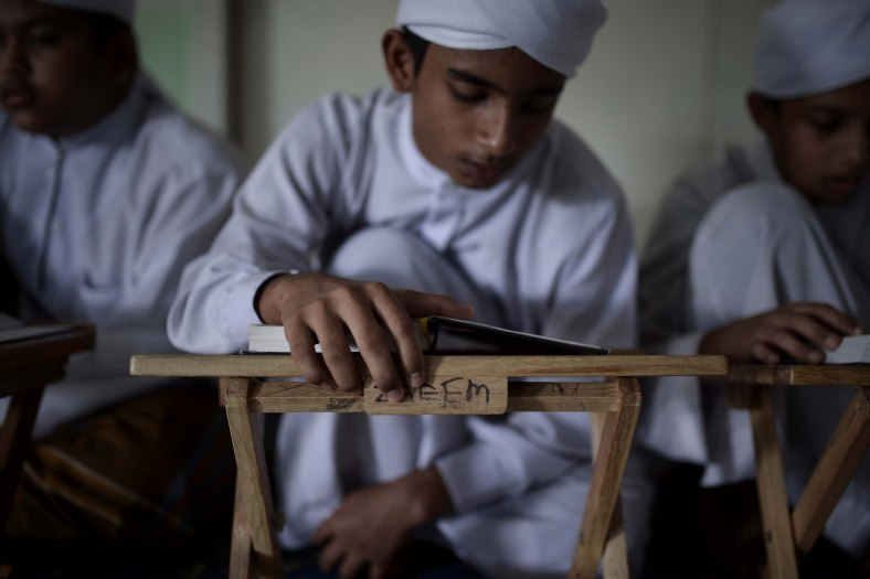 A Malaysian religious student reads the Koran at school during the Muslim holy fasting month of Ramadan in Sungai Buloh, suburb of Kuala Lumpur on July 08, 2014. Ramadan is the ninth month of the Islamic calendar, Islam's holy month of Ramadan is celebrate by Muslims worldwide mark by fasting, abstain from eating, drinking, having sex and smoking from dawn to dusk to cleanse the soul and strengthen the spiritual bond between them and the almighty. Photo Adib Rawi Yahya