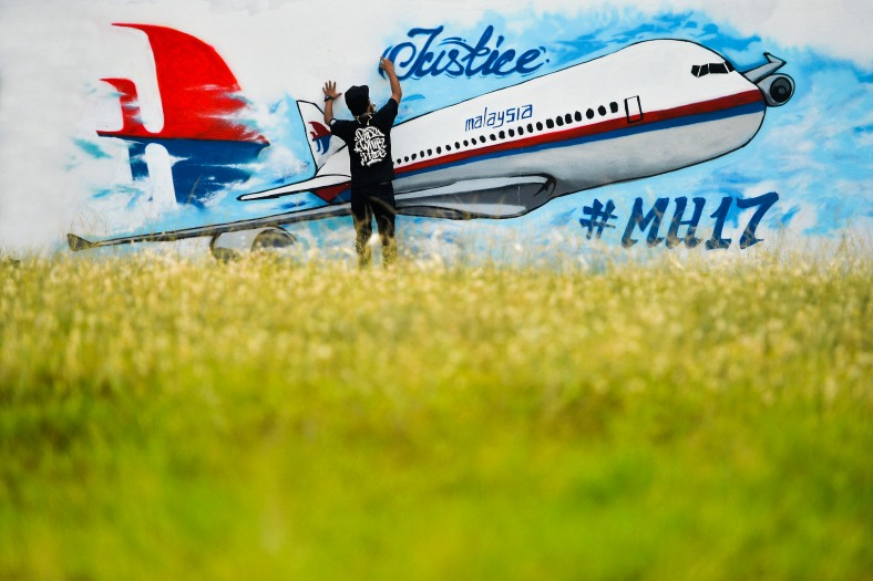 A man works on a graffiti featuring the Malaysia Airlines flight MH17 which crashed over Ukraine, in Kuala Lumpur on July 26, 2014. Malaysia Airlines Flight 17 was a scheduled international passenger flight from Amsterdam to Kuala Lumpur that crashed on 17 July 2014. The plane is believed to have been shot down with a Buk surface-to-air missile and killing all 283 passengers and 15 crew on board. The crash occurred in the conflict zone of the ongoing Donbass insurgency, in an area controlled by the Donbass People's Militia. Photo Adib Rawi Yahya