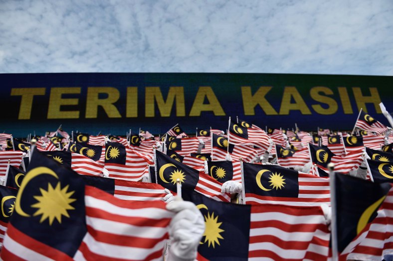 Student hold Jalur Gemilang during the 57th Merdeka celebrations at Dataran Merdeka in Kuala Lumpur on August 31, 2014. 'Malaysia...Di Sini Lahirnya Sebuah Cinta' is the official theme of this year's Merdeka. The theme is taken from the lyrics of the song 'Warisan' popularised by the late Sudirman Haji Arshad. Photo Adib Rawi Yahya