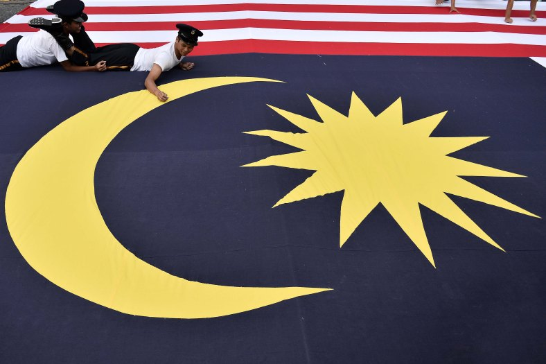 Participant make final checks of the giant National flag during the 57th Merdeka celebrations at Dataran Merdeka in Kuala Lumpur on August 31, 2014. 'Malaysia...Di Sini Lahirnya Sebuah Cinta' is the official theme of this year's Merdeka. The theme is taken from the lyrics of the song 'Warisan' popularised by the late Sudirman Haji Arshad. Photo Adib Rawi Yahya