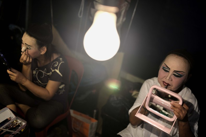 A Chinese opera actress puts on make-up at a makeshift theater during Chinese Hungry Ghost Festival outside Kuala Lumpur on August 06, 2014. In the Chinese tradition the seventh month of the lunar year is regarded as the Ghost Month in which spirits and ghosts come down to earth. The devotees also will do a ritualistic food offerings, burning incense, burning joss paper and burning a paper-made models such as clothes, gold, sport cars and other fine goods to appease wandering spirits. Photo Adib Rawi Yahya