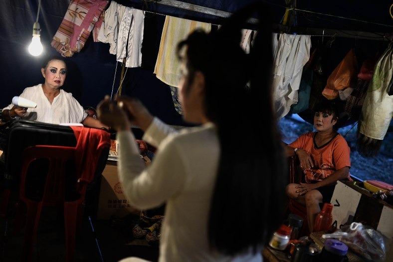 A Chinese opera actress prepare themselves before performs at a makeshift theater during Chinese Hungry Ghost Festival outside Kuala Lumpur on August 06, 2014. In the Chinese tradition the seventh month of the lunar year is regarded as the Ghost Month in which spirits and ghosts come down to earth. The devotees also will do a ritualistic food offerings, burning incense, burning joss paper and burning a paper-made models such as clothes, gold, sport cars and other fine goods to appease wandering spirits. Photo Adib Rawi Yahya