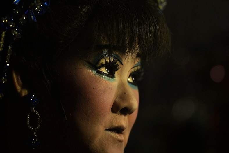 A Chinese opera actress waits for his turn to performs at a makeshift theater during Chinese Hungry Ghost Festival outside Kuala Lumpur on August 06, 2014. In the Chinese tradition the seventh month of the lunar year is regarded as the Ghost Month in which spirits and ghosts come down to earth. The devotees also will do a ritualistic food offerings, burning incense, burning joss paper and burning a paper-made models such as clothes, gold, sport cars and other fine goods to appease wandering spirits. Photo Adib Rawi Yahya