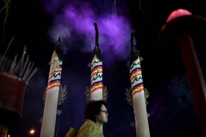 An Ethnic Chinese devotee walks pass the large joss sticks after prayers during Chinese Hungry Ghost Festival inside Kuala Lumpur on August 04, 2014. In the Chinese tradition the seventh month of the lunar year is regarded as the Ghost Month in which spirits and ghosts come down to earth. The devotees also will do a ritualistic food offerings, burning incense, burning joss paper and burning a paper-made models such as clothes, gold, sport cars and other fine goods to appease wandering spirits. Photo Adib Rawi Yahya