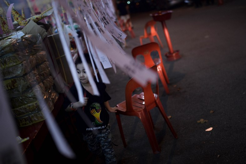 A young Ethnic Chinese devotee ran close to the paper-made statue during Chinese Hungry Ghost Festival inside Kuala Lumpur on August 04, 2014. In the Chinese tradition the seventh month of the lunar year is regarded as the Ghost Month in which spirits and ghosts come down to earth. The devotees also will do a ritualistic food offerings, burning incense, burning joss paper and burning a paper-made models such as clothes, gold, sport cars and other fine goods to appease wandering spirits. Photo Adib Rawi Yahya